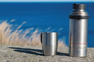 Stainless steel thermos and coffee mug sitting on a rock