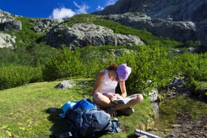 Hiker reading a book in the mountains