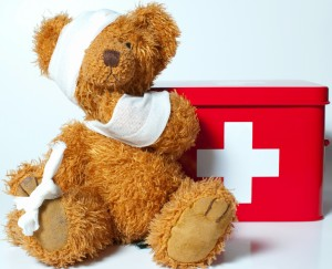 Teddy bear with bandages and first aid kit