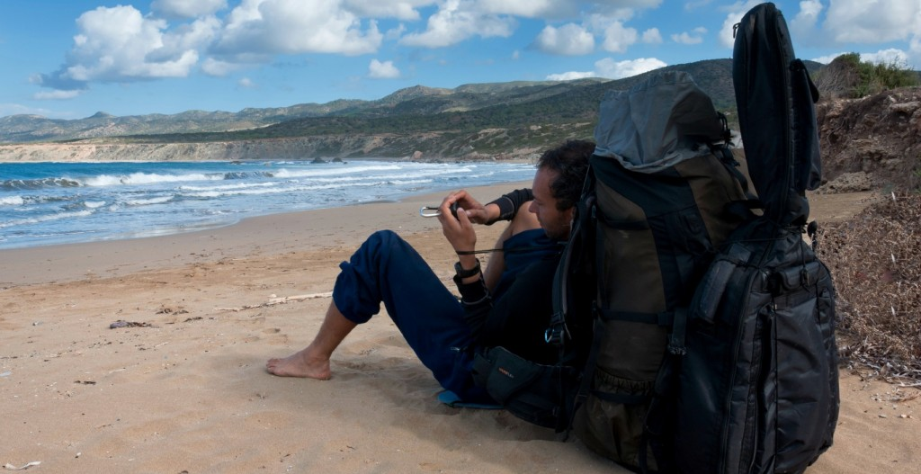 Hiker sitting with an oversized backpack and guitar on the beach