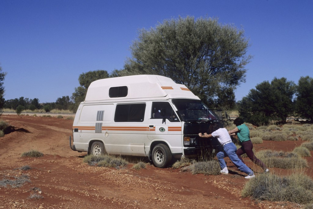 Two people pushing a camper van out of the dirt road