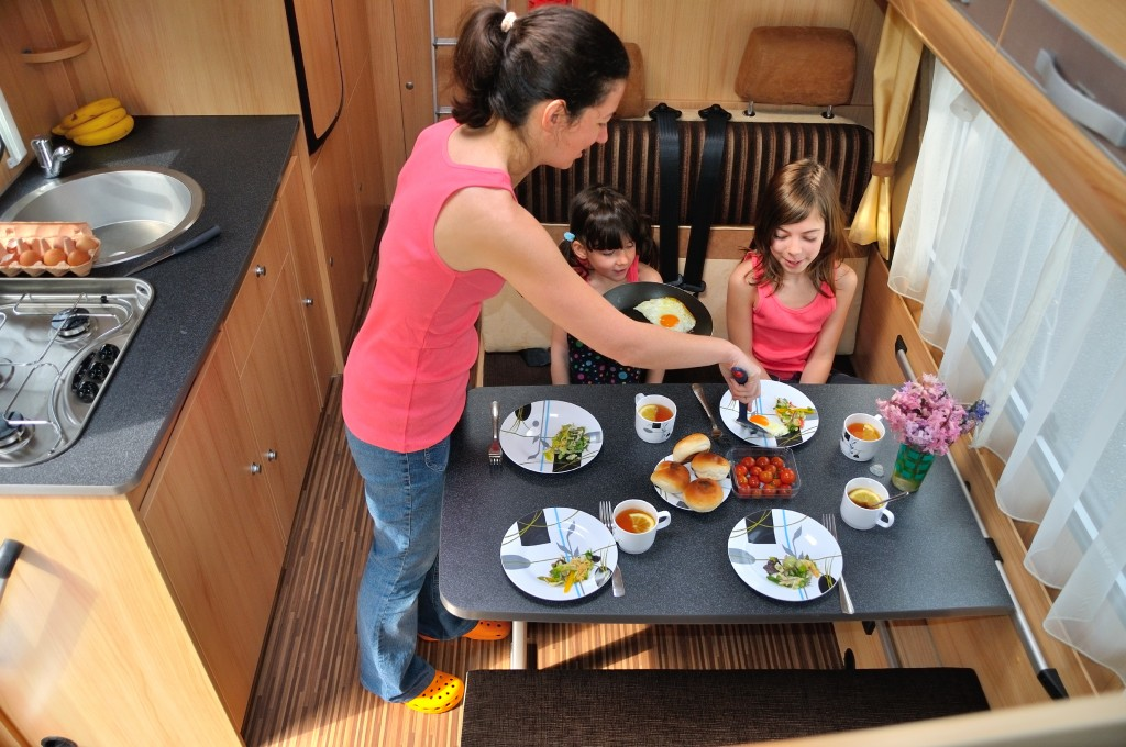 Family eating a camp style meal in a camper kitchen