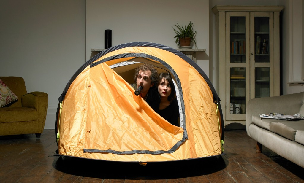 couple in tent that is set up in the living room