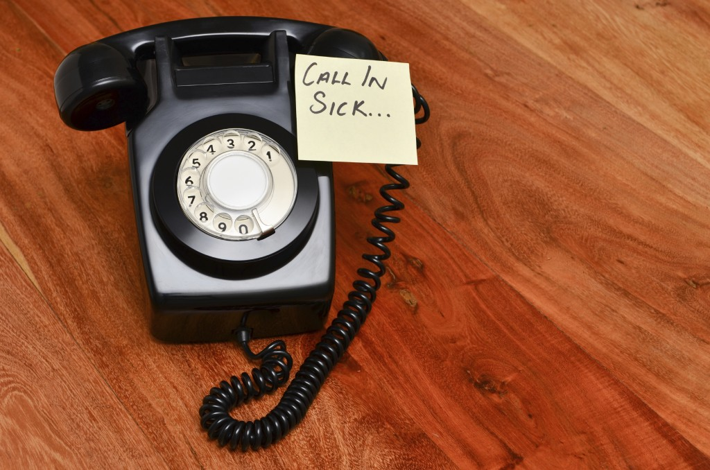 Rotary telephone with a post it reminding you to call in sick