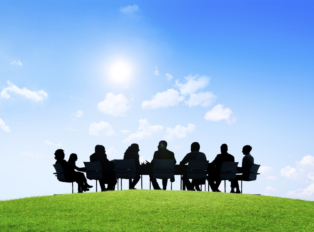 People sitting around a meeting table in the outdoors and under the sunshine