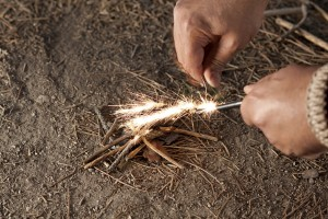 Person using a fire starter on a small batch of kindling