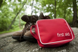First aid kit sitting against a pair of hiking boots outside