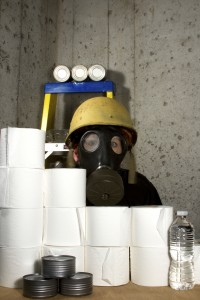 Person wearing a gas mask with survival items such as toliet paper, water and canned goods