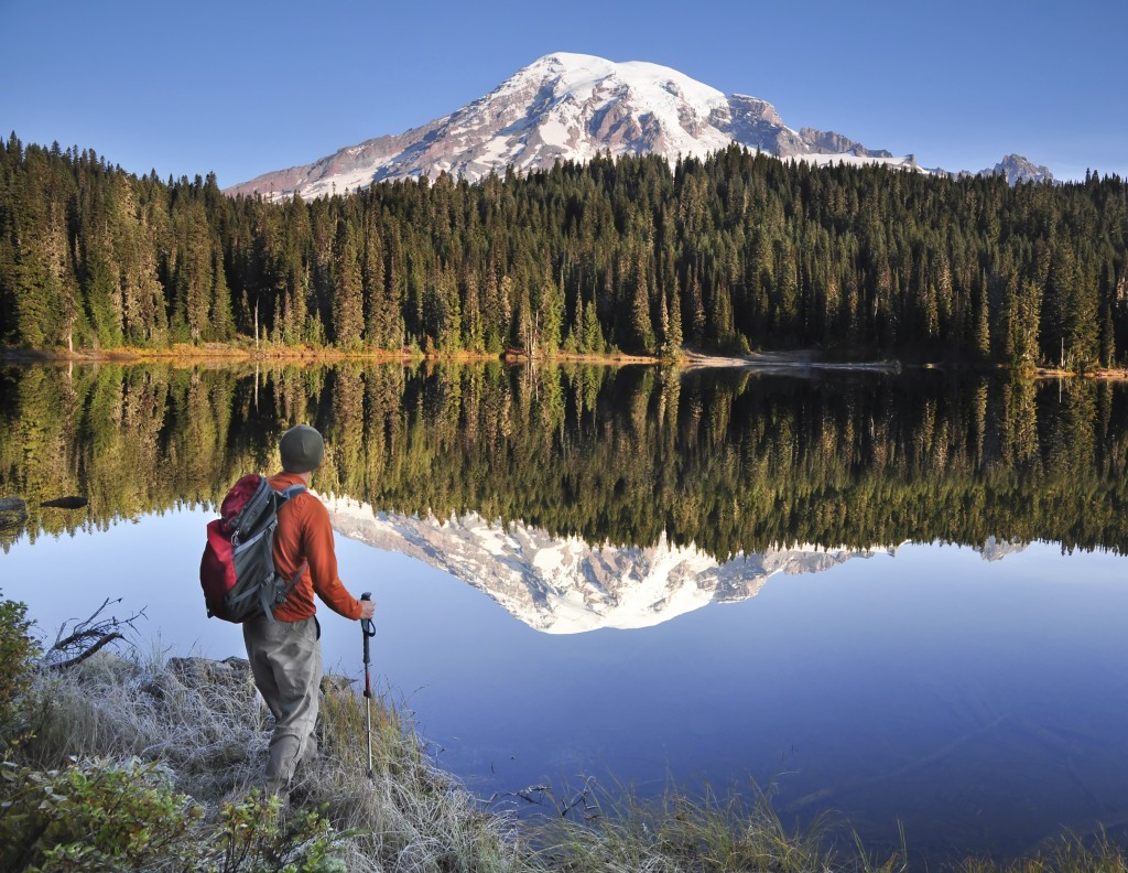 Backpacker looking at Mt Rainier and its reflection in a lake