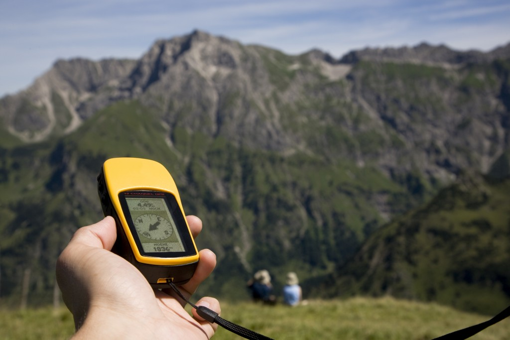 Person holding a GPS unit in the mountains