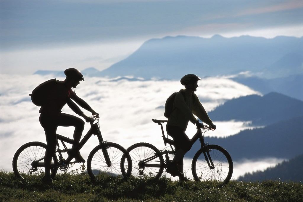 2 mountain bikers taking a break on a ridge looking down into a mountainous valley
