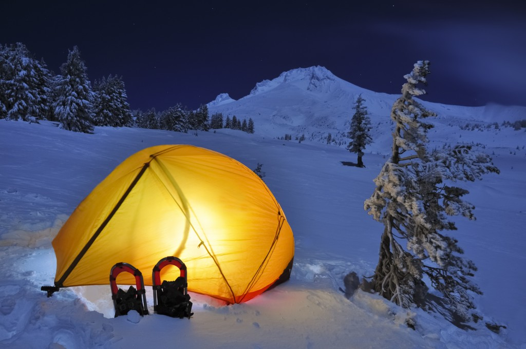 Tent set up on the snow at the base of a mountain with a light on inside