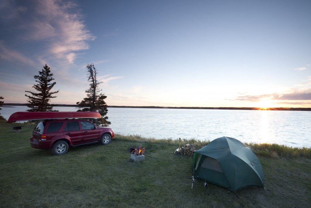 Camping spot along the water with a tent and canoe over the car