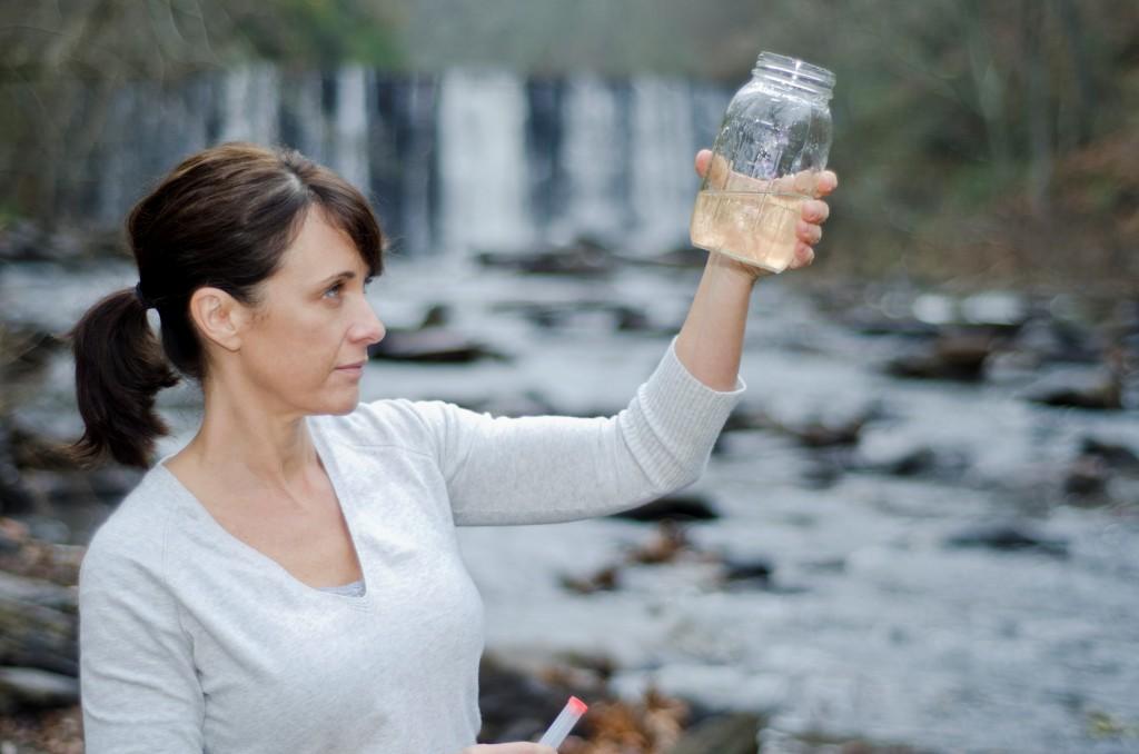 Environmental researcher sampling water on a creek