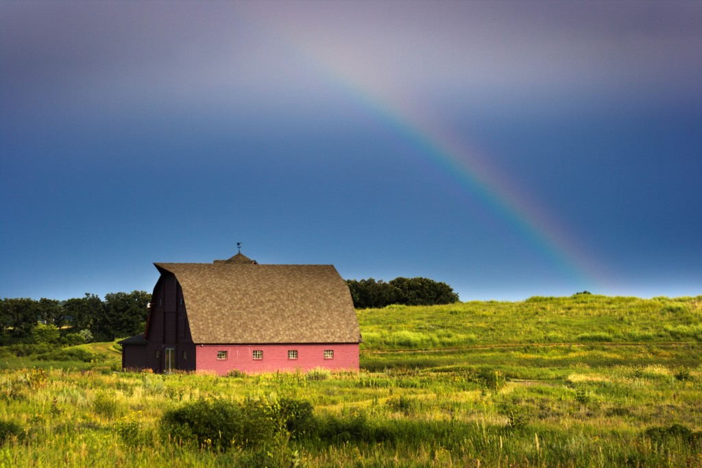 Midwest prairie landscape with barn and rainbow