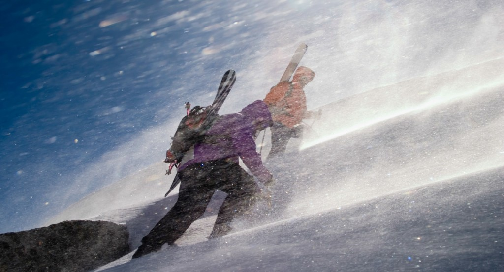 Skiers climbing a mountain in a winter storm
