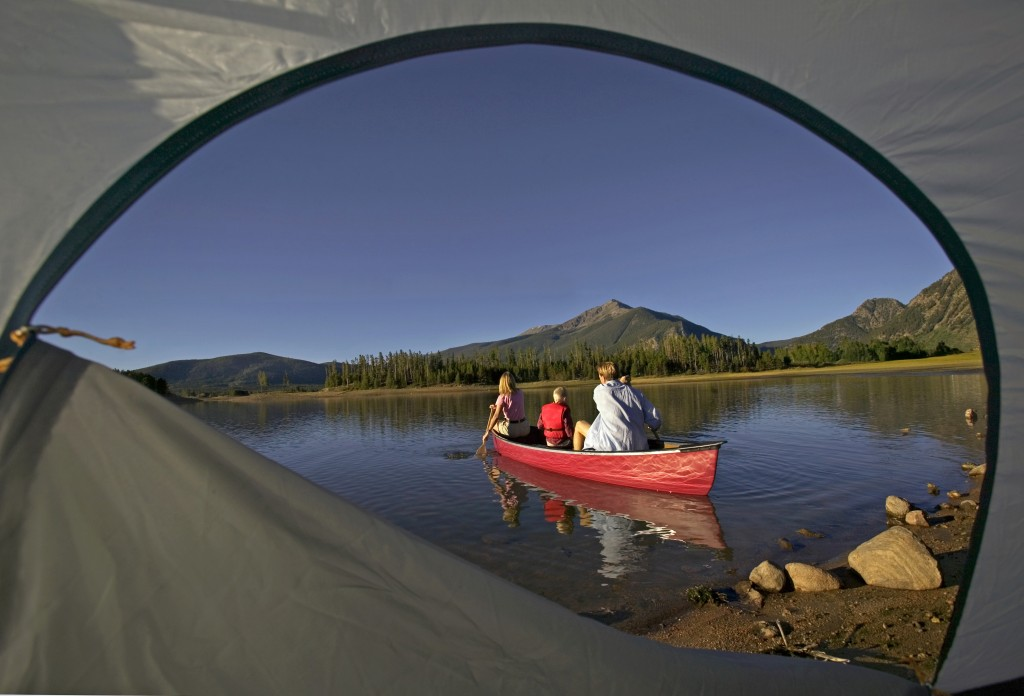 Family canoeing with beautiful weather as seen through a tent