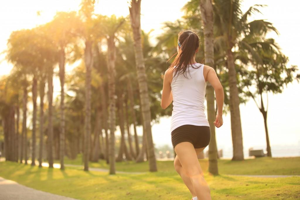 Woman jogging outside in tree lined street