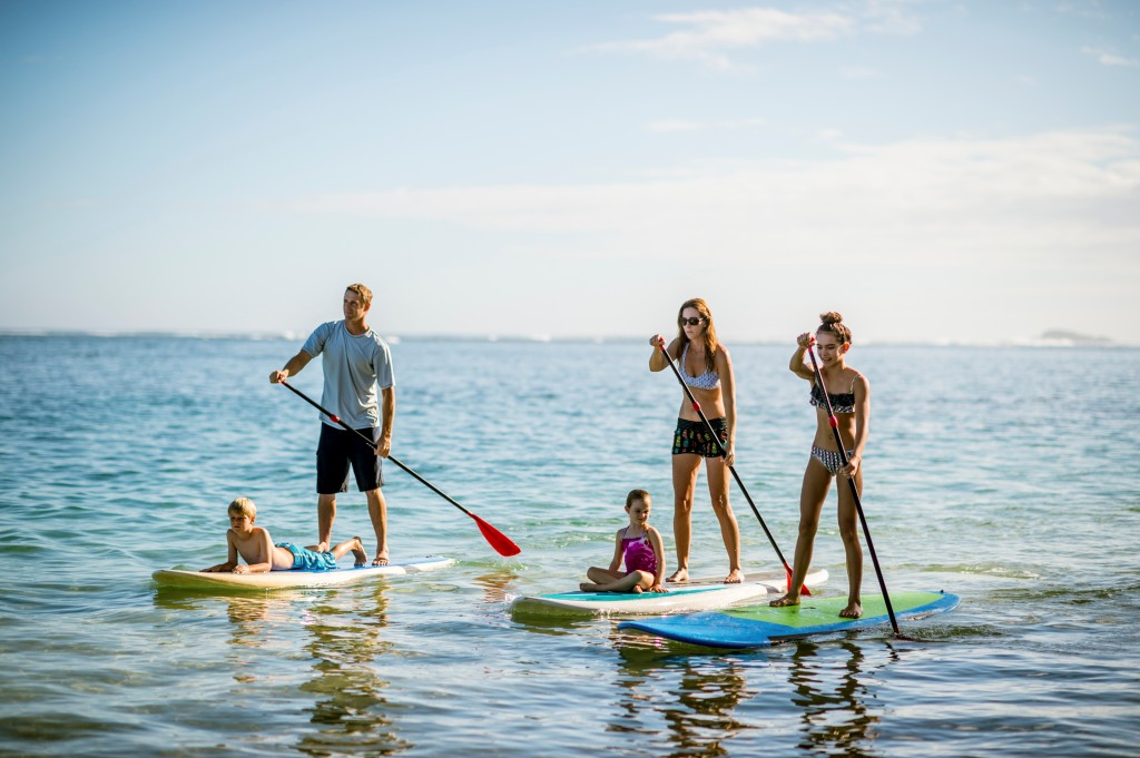 Family on stand up paddle boards with kids on the board