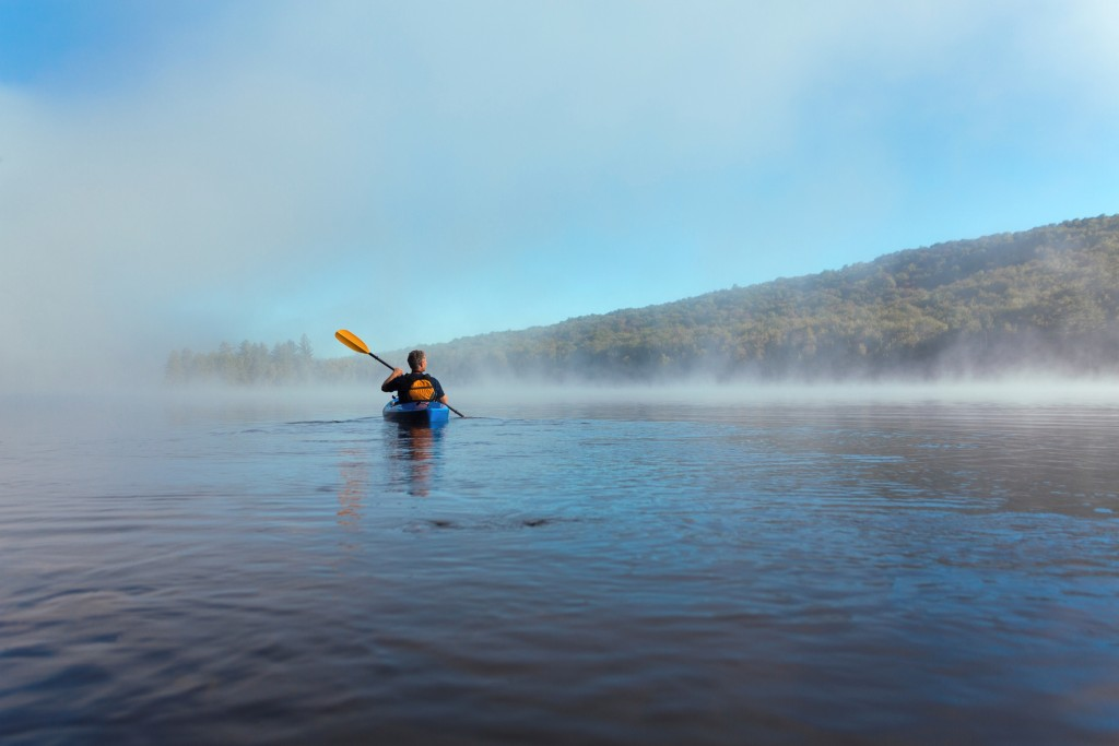 Person kayaing on a lake with low morning fog