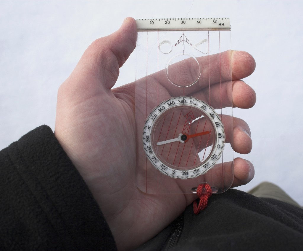 Person holding a compass to take a bearing