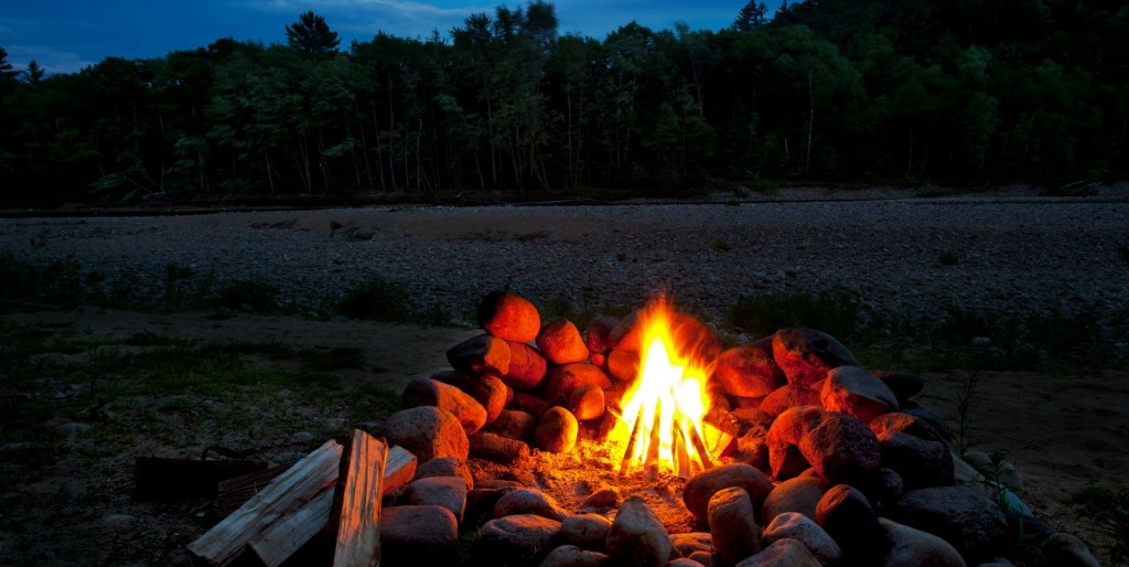 camp fire  with wood next to the stone fire ring