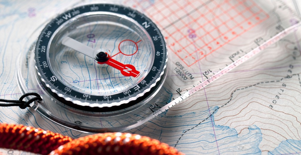 Compass and climbing rope on a topography map