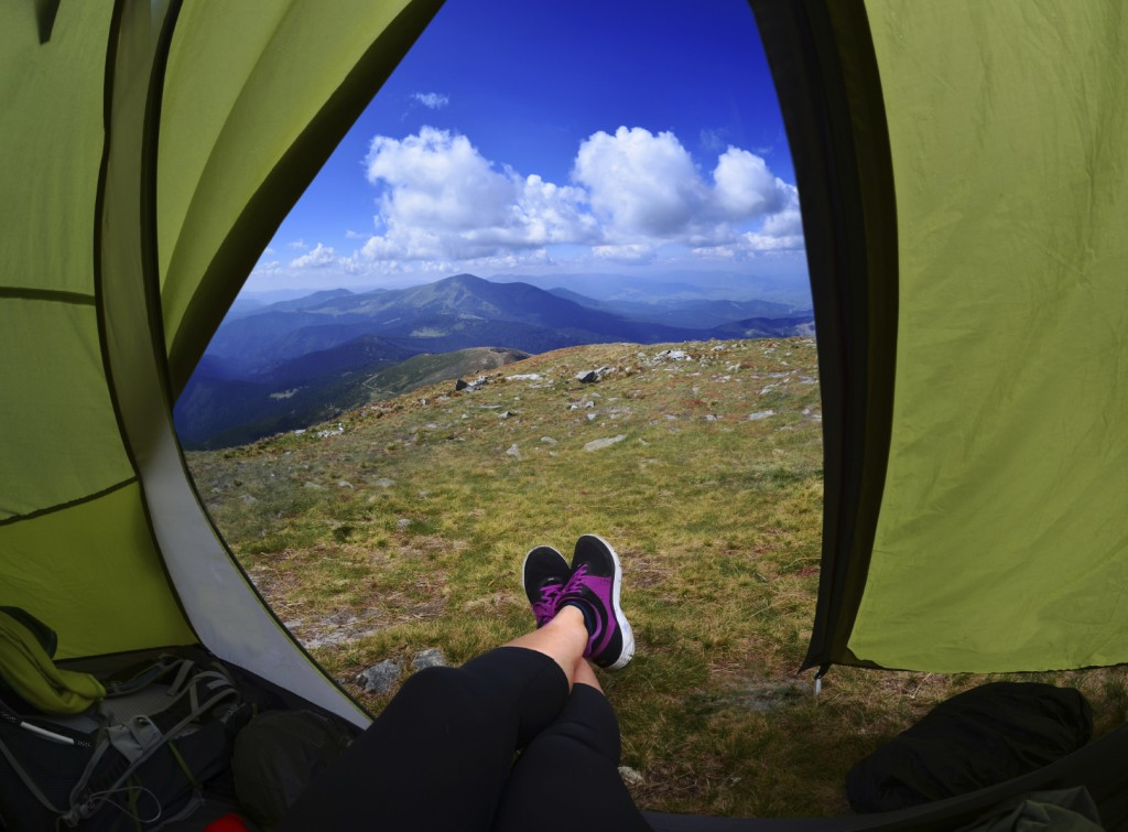 Woman lying in tent with a view of mountain and sky