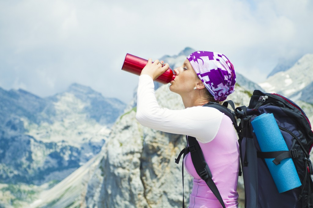 Hiker drinking water in the mountains