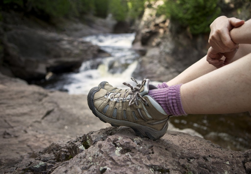Hiker with boots sitting by a river