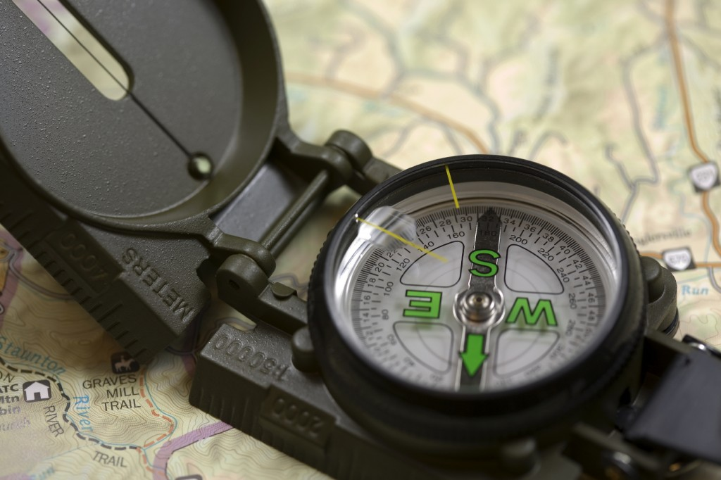 Hikers compass sitting on a map