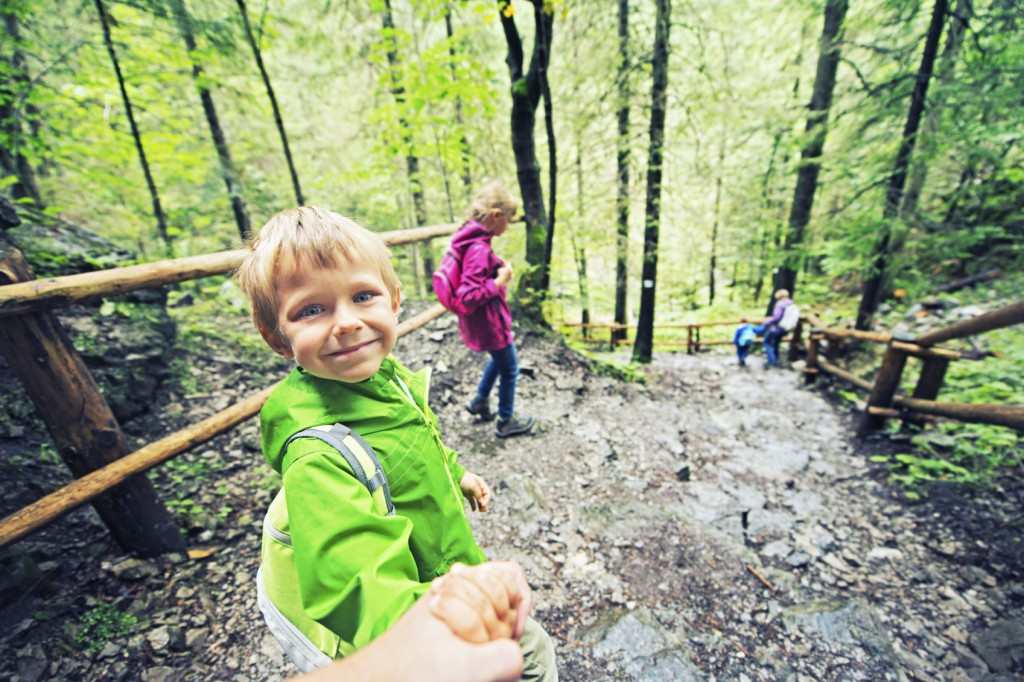 boy smiling on a hike in the woods