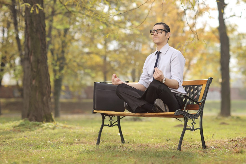 Businessman meditating seated on a bench in park