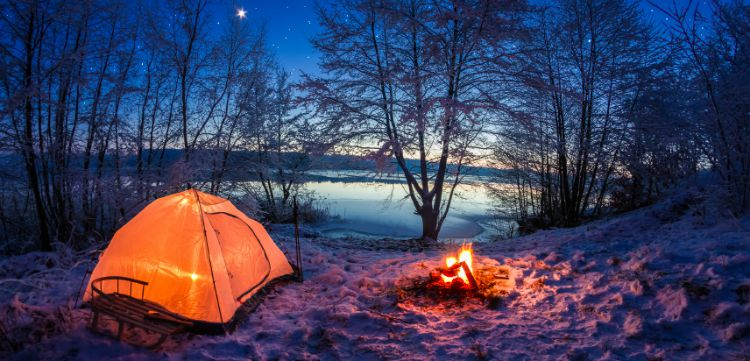 Camping on a lake with a tent and camp fire