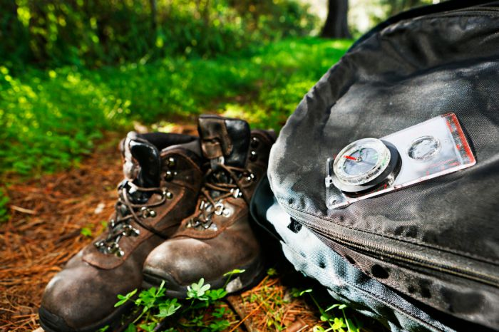 Hiking gear on a trail - books, pack, compass