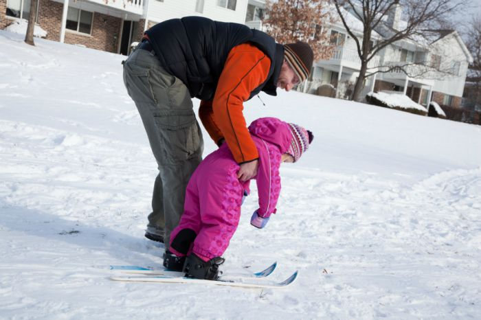 A parent teaching their kid how to ski.