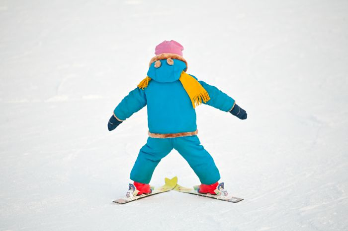little child doing his first downhill on alpine skis, standing back closeup on snow background